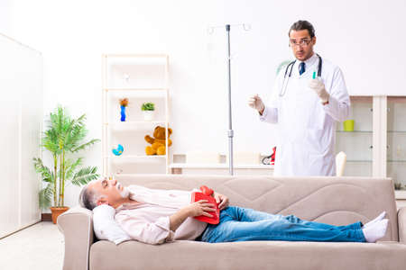 Young male doctor visiting old patient at home Stockfoto