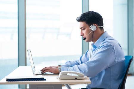 Male call-center operator in business concept