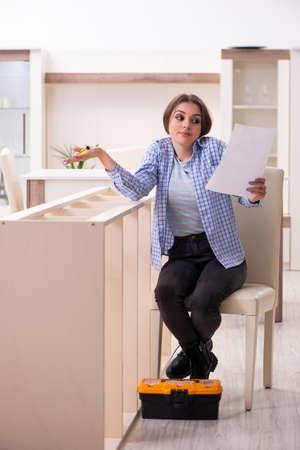 Jeune belle femme assemblant des meubles à la maison
