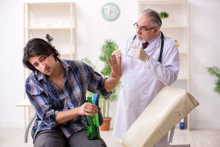 Young male alcoholic visiting old doctor