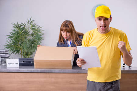 Young male courier delivering box to hotels reception