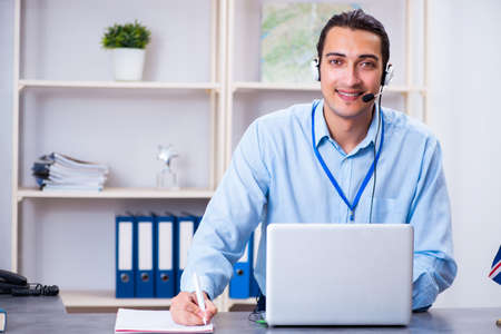 Young male travel agent working in the office