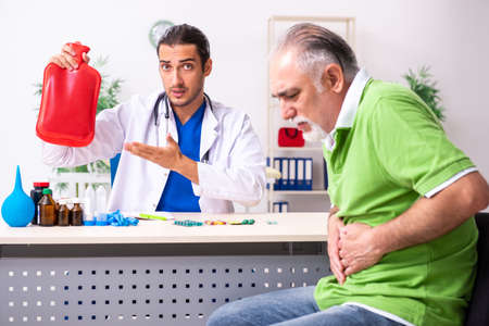 Old man visiting young male doctor gastroenterologist