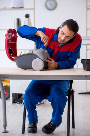 Young male contractor repairing vacuum cleaner at workshop