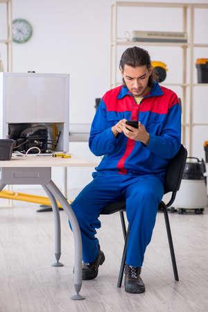 Junger männlicher Auftragnehmer, der Kühlschrank in der Werkstatt repariert Standard-Bild