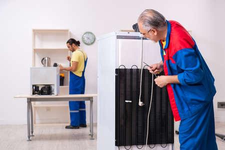 Two contractors repairing fridge at workshop Reklamní fotografie