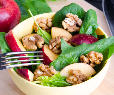 The spinach salad with nuts and apples served on table Imagens