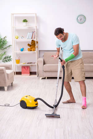 Young injured man cleaning the house Foto de archivo - 134292668