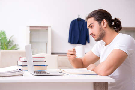 Young male student preparing for exams at home Stock Photo