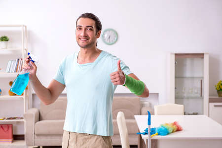 Young injured man cleaning the house Foto de archivo - 134292849