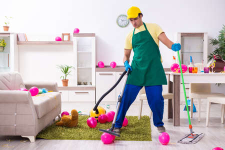 Young male contractor doing housework after party Foto de archivo - 134376788
