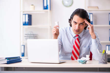 Young male employee suffering in the office Banco de Imagens