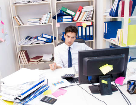 Businessman working in the office with piles of books and papers Banque d'images