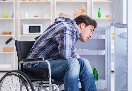 Young disabled injured man opening the fridge door 스톡 콘텐츠