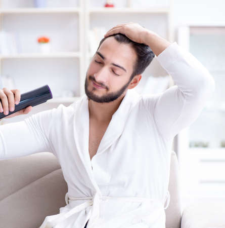Young man drying hair at home with a hair dryer blower Фото со стока
