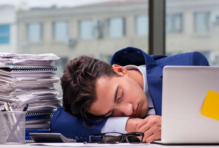 Workaholic businessman overworked with too much work in office Banco de Imagens