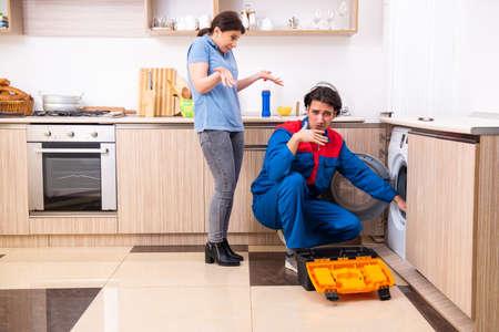 Young male repairman repairing washing machine