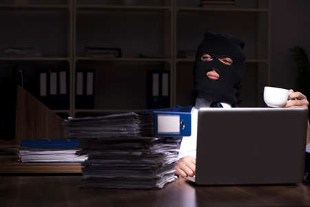 Male employee stealing information in the office night time 스톡 콘텐츠