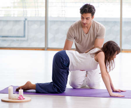 Personal trainer assisting during exercise in sports gym
