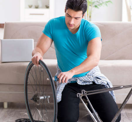 Young man repairing bicycle at home
