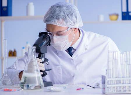 El hombre en el laboratorio probando una nueva solución de limpieza detergente Foto de archivo