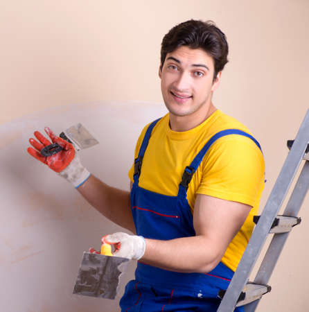 Young contractor employee applying plaster on wall Standard-Bild