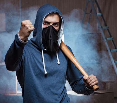 Hooligan with bat in dark room 版權商用圖片