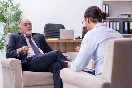 Anciano visitando joven médico psicólogo