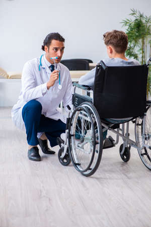 Young male doctor pediatrist and boy in wheel-chair