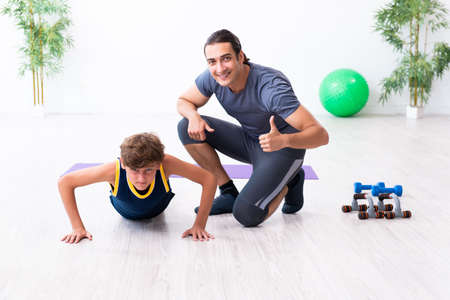 Young father and his son doing exercises