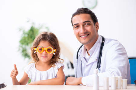 Young doctor pediatrician with small girl