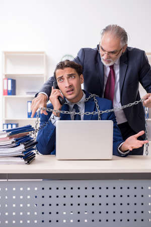 Old boss and young male employee in the office Stock Photo