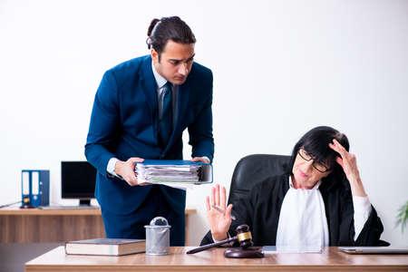 Young intern asking senior judge for advice Stockfoto