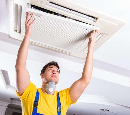 Repairman repairing ceiling air conditioning unit Stock Photo