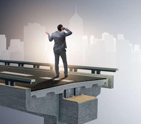 The businessman in uncertainty concept with broken bridge
