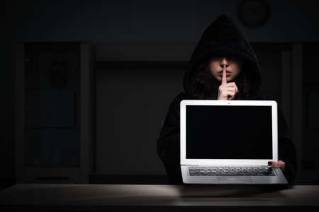 The female hacker hacking security firewall late in office Stock Photo