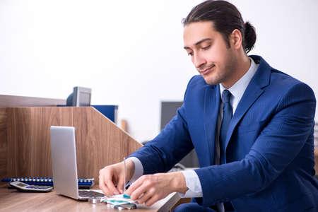 Junger gutaussehender Geschäftsmann, der im Büro arbeitet