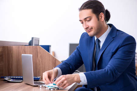 Young handsome businessman working in the office