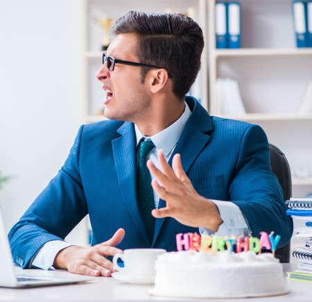 Junger Geschäftsmann, der Geburtstag allein im Amt feiert