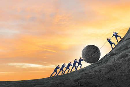 El ejemplo del trabajo en equipo con empresarios empujando la piedra hacia la cima