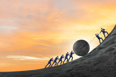 The teamwork example with business people pushing stone to top