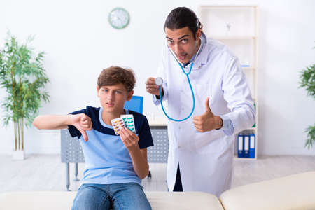 Young male doctor examining boy in the clinic