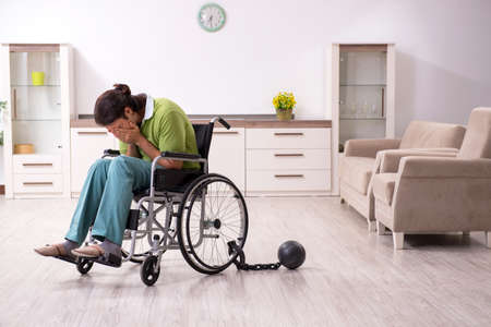 Young male invalid in wheelchair suffering at home Zdjęcie Seryjne - 138513151