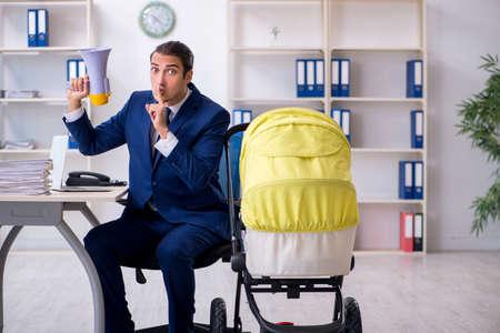 Jeune père s'occupant du nouveau-né au bureau
