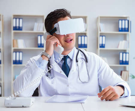 Young doctor with vr virtual reality headset working in the office