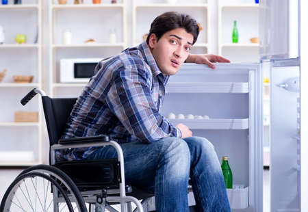 Young disabled injured man opening the fridge door Zdjęcie Seryjne
