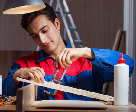 The young man gluing wood pieces together in diy concept