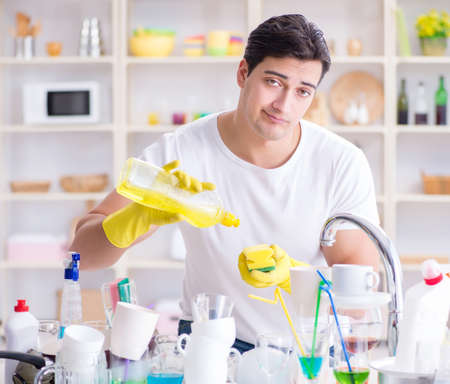 Man frustrated at having to wash dishes Stock Photo