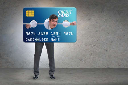 Businessman in credit card burden concept in pillory