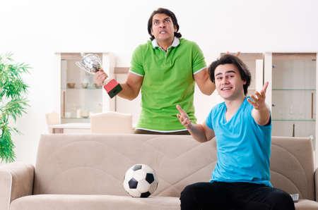 Amis regardant le football à la maison